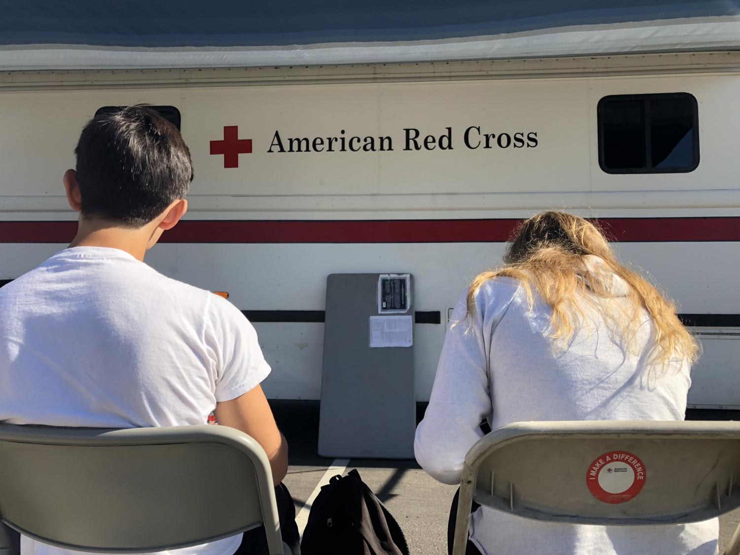 Students+fill+out+forms+and+wait+in+front+of+the+American+Red+Cross+blood+drive+bus+for+their+turn+to+give+blood.+On+Wednesday%2C+Dec.+19%2C+students+left+classes+throughout+the+day+to+donate+their+blood+to+the+cause.