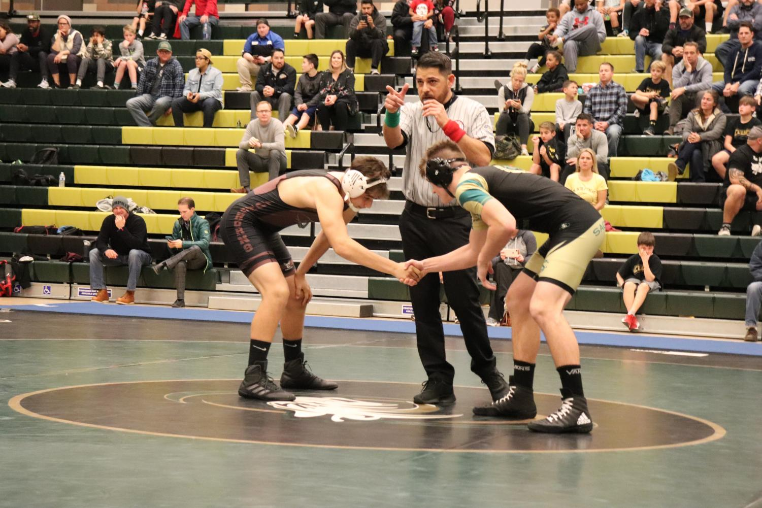 Freshman+Luke+McLellan+shakes+hands+with+his+opponent+before+the+referee+blows+the+whistle.+McLellan+wrestled+in+the+170+weight+class+and+won+this+match+with+a+pin.