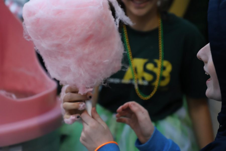 Freshman Zoebelle serves cotton candy to little kids before the start of the game. The athletic mall was filled with booths ranging in candy to games, to satisfy each students perfect idea of Hoopcoming.
