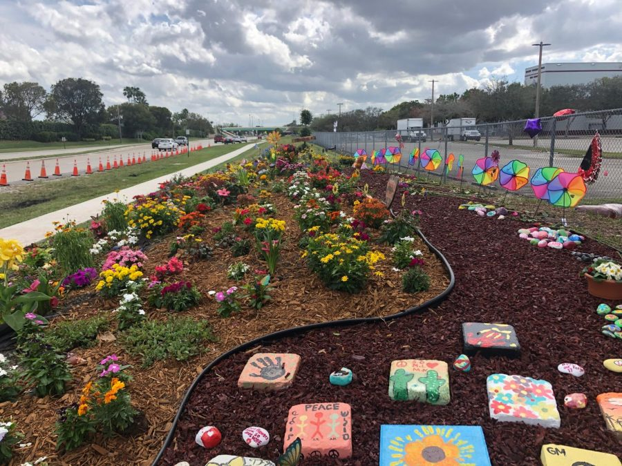 Assorted flowers grow in front of Marjory Stoneman Douglas High School alongside stones and garden decor all in honor and memory of those who were lost in the Parkland Shooting that took place a year ago, last Thursday. The idea of this on campus memorial originated from Douglas High teacher Ronit Reoven and senior Victoria Gonzales (girlfriend of Joaquin Oliver who was lost in the shooting).