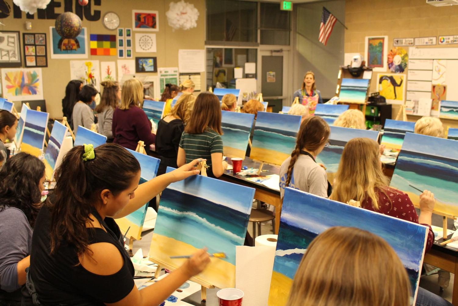 Students+and+community+members+follow+along+with+Mrs.+Herrick+as+she+teaches+them+to+paint+a+beach+scene.+The+Arts%E2%80%99s+department+held+its+annual+paint+night+fundraiser+on+Friday+to+raise+money+for+the+program.