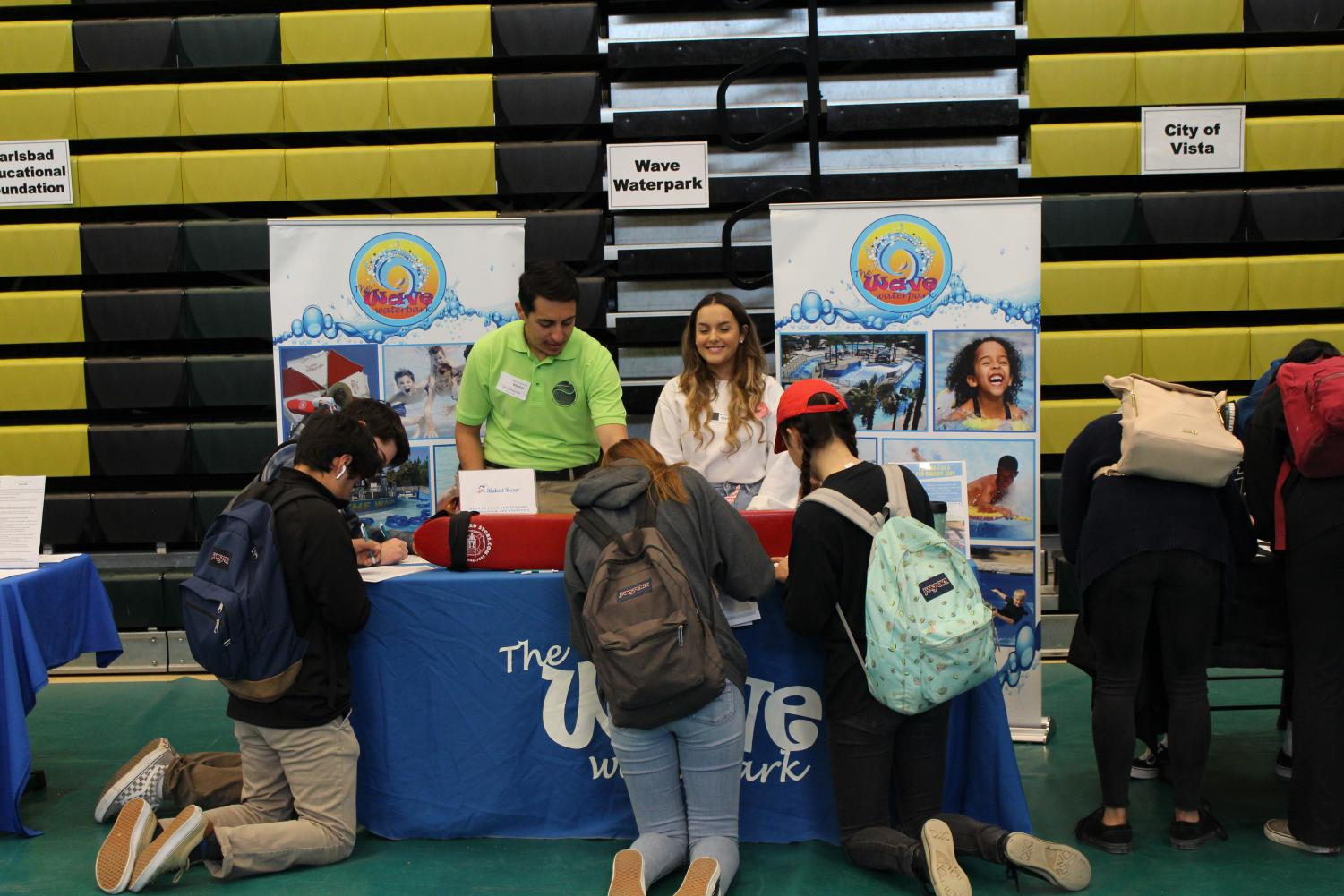 Students+kneel+before+the+Wave+Waterpark+stand+to+fill+out+job+applications.+Students+attended+the+Jive+Expo+in+the+Bobcat+arena+to+find+potential+job%2C+community+service%2C+and+internship+opportunities.+