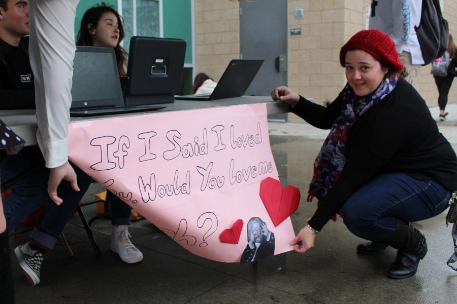 Ms. Quinones, the choir director, holds up the Valentines grams sign on a windy Monday morning. Choir is selling Valentines grams until Feb. 13 to raise money for the choir program and spread a little love around the campus.
