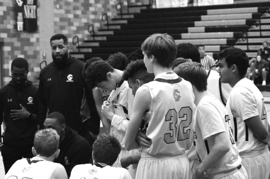 Varsity head coach Brandon Dowdy talks strategy as the Bobcats take a time out. During the team talk the players gather together to exclude the distractions and keep their head in the game.
