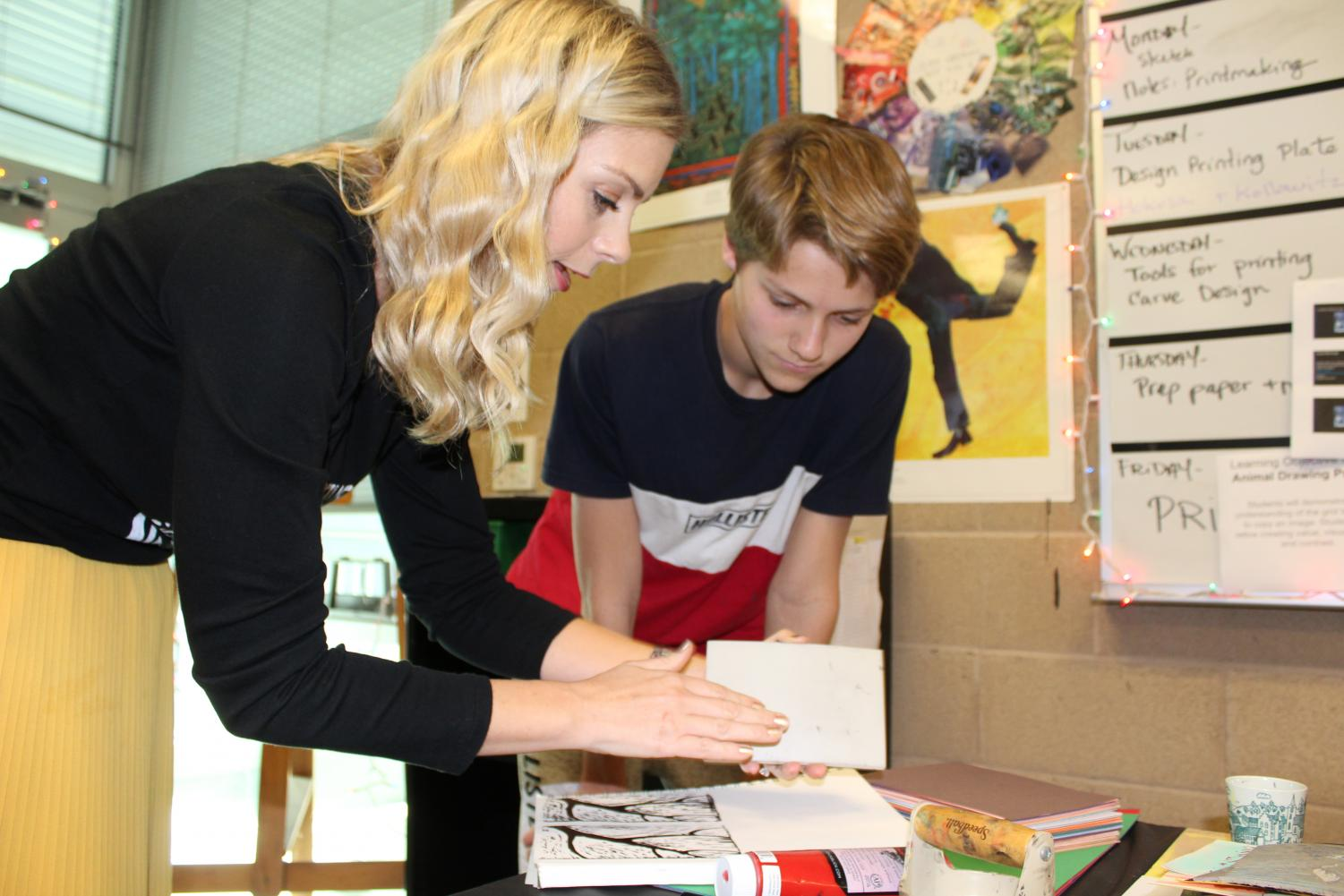 Megan Herrick helps a student create a piece of art during class. She gave him new ideas and helpful guidance for finishing his artwork.