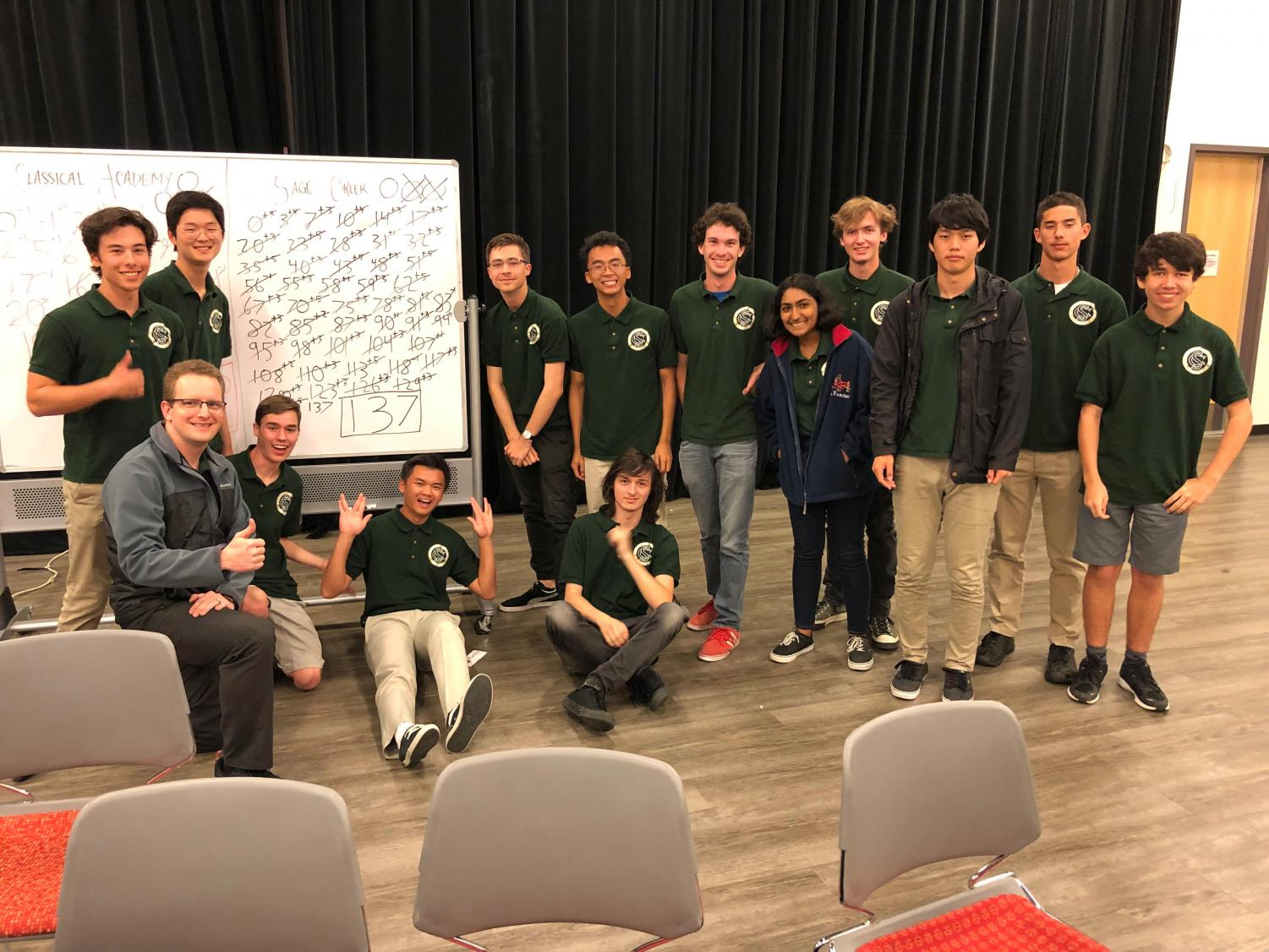The team poses after winning their play-in match to participate in the championship tournament. The 137 score on the whiteboard not only marks the win of the match, but the highest score in the teams history.