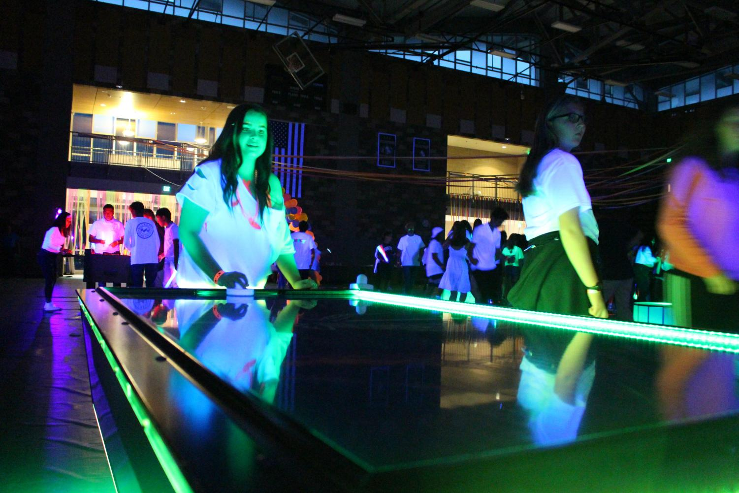 Students+take+a+break+from+dancing+and+play+light+up+neon+air+hockey+during+MORP.+The+dance+also+included+activities+such+as+foosball+and+a+photobooth+for+students+to+participate+in.