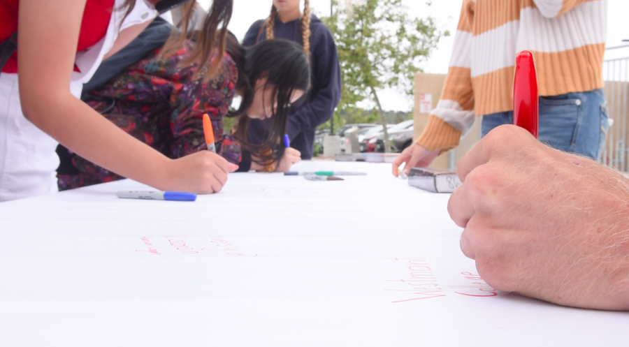 "Senior Danny Rubin scribbles, ""Westmont College"" on the 2019 graduating class's post secondary plans' poster. All of the seniors gathered in front of the Performing Arts Center after the most recent advisory period in order to participate in the school wide ""college signing day."""