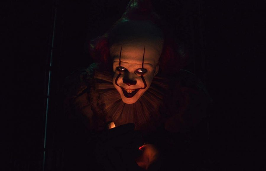 "Pennywise reveals himself hiding beneath the bleaches. After his gloved hands snatched a firefly from the air, Pennywise opened his palms, illuminated his face, and said a friendly, ""Hello."""