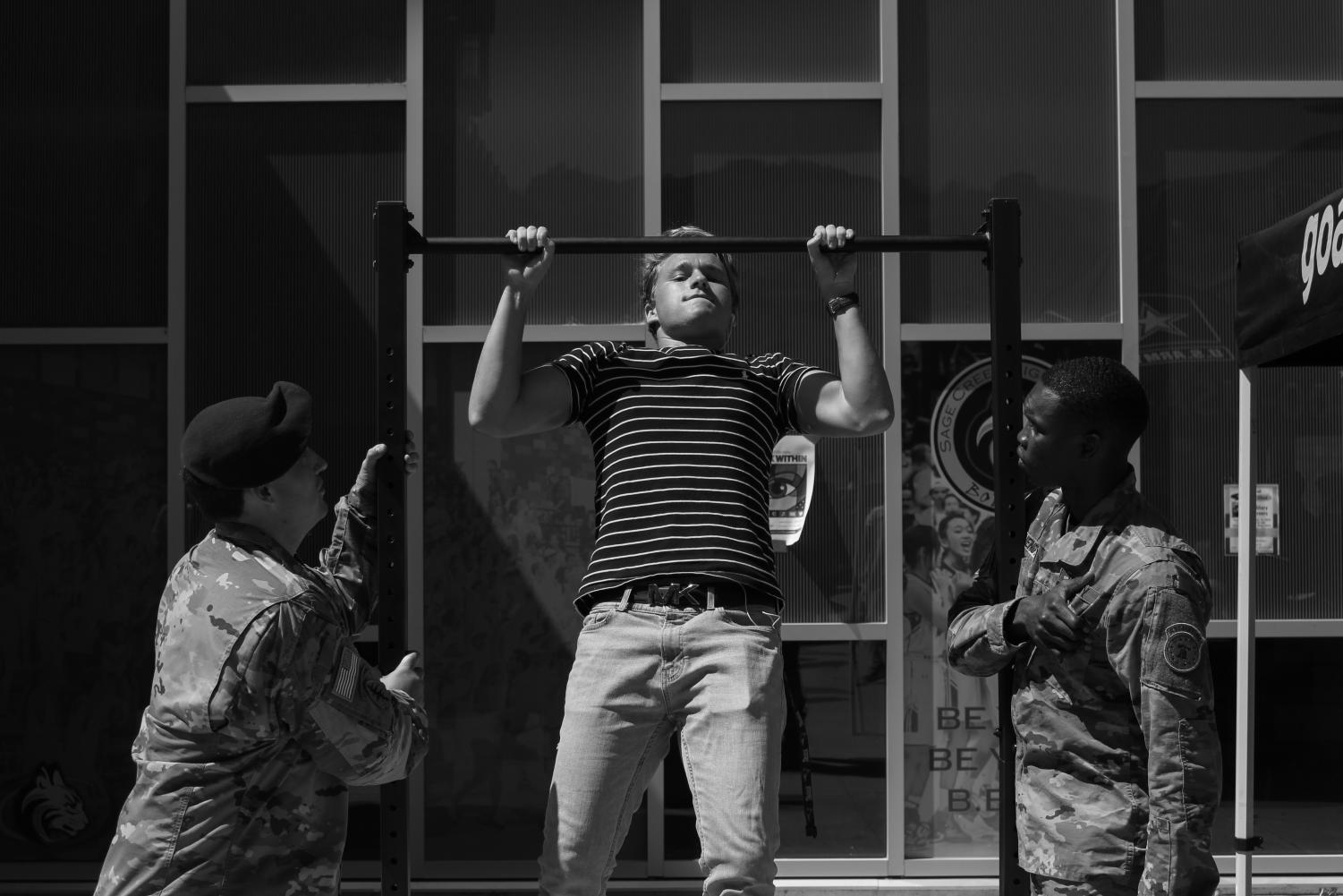 Senior+Jonah+Shoemaker+tests+his+strength+in+front+of+two+Army+soldiers+on+the+pull-up+bars.+Army+recruiters+visited+during+lunch+on+Wednesday%2C+Sept.+18.
