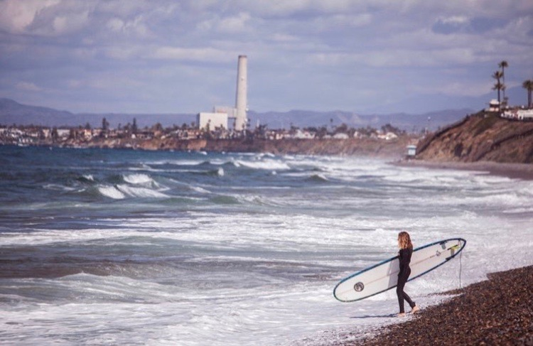 A team member gets ready to paddle out for a session. The club meets weekly for practices and get-togethers at local beaches.