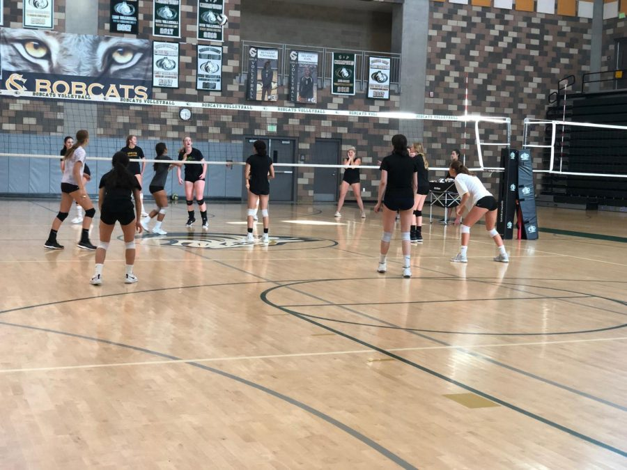 Sophomore Bethany Tomaneng (grey shirt, far side) prepares to set senior Claire Perhach (black shirt, nearest to Bethany) as they work hard in preparation for the upcoming week. They practiced on Friday, Sept. 20 in preparation for their game on Monday, Sept. 23.