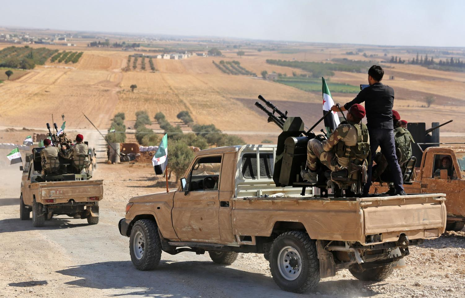 Syrian Rebels ride into the Syrian-Turkish border, backed by Turkey. On Oct. 9, Turkish Troops moved past the border into Syria.