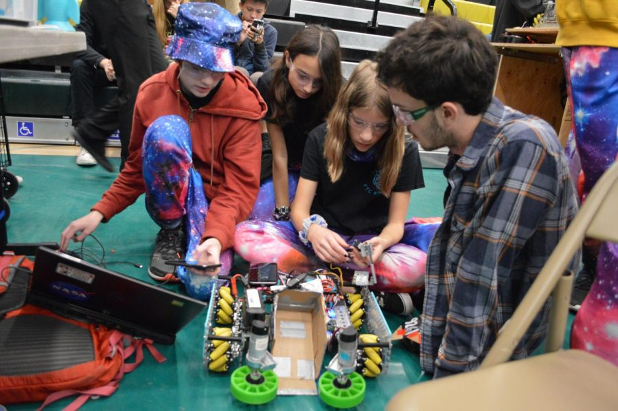 Team Level Up gathers around their robot to access hardware and software problems. Later on in the competition day, Level Up strived to semi-finals.