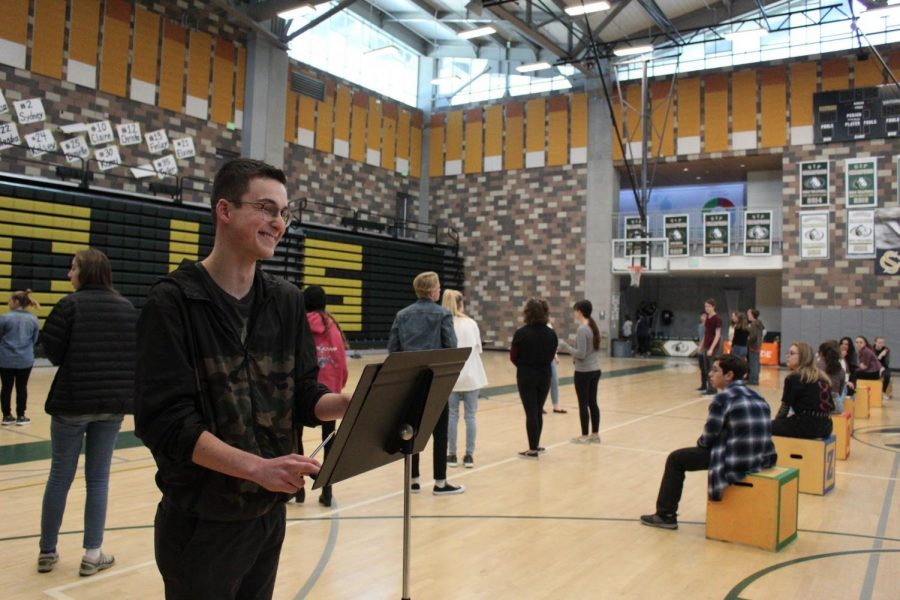 "Junior Nicholas Tappin helps conduct the pit orchestra as the Matilda cast rehearses in the gym. They will be performing ""Revolting Children"" at the pep rally on Friday."