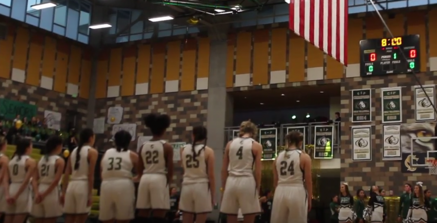 Girls varsity basketball stands for the National Anthem at their Hoopcoming game against Oceanside. The lady bobcats triumphed over their rivals with a score of 50-47.