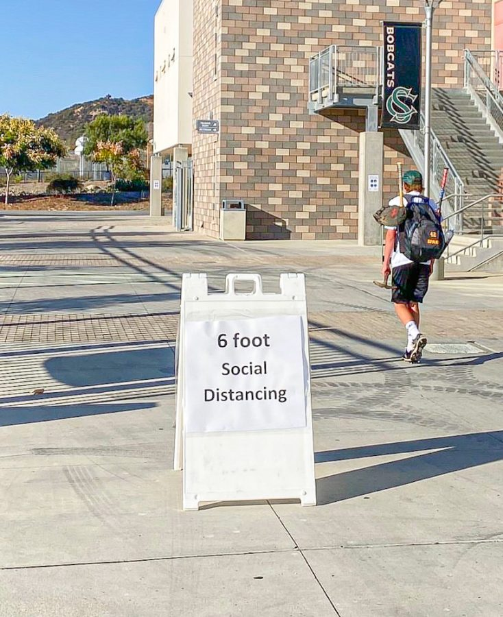 A student heads to practice while passing a sign reinforcing social distancing on Oct. 13. Social distancing is one of the ten protocols to ensure on-campus safety.