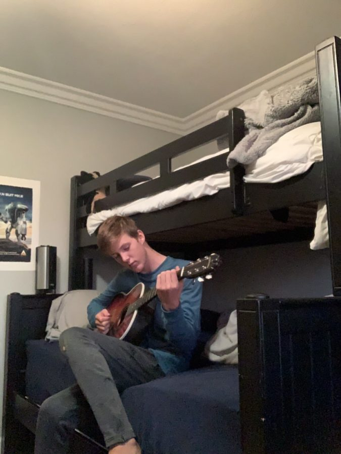 Freshman Blake Hafner practices on his guitar. Looking down at it and expressing his enjoyment for music.