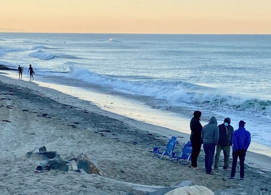 A small group of men are gathered in prayer during sunrise while two Sage Creek freshmen head out to surf. Despite the weather getting colder, surfers still enjoy the winter swells.