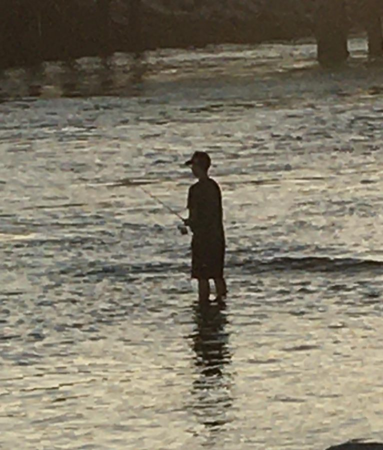 During COVID-19, due to social distancing rules solo water activities are very popular such as fishing. This teenager at the rivermouth that leads to the Batiquitos Lagoon from Ponto Beach is seen fishing for fun.