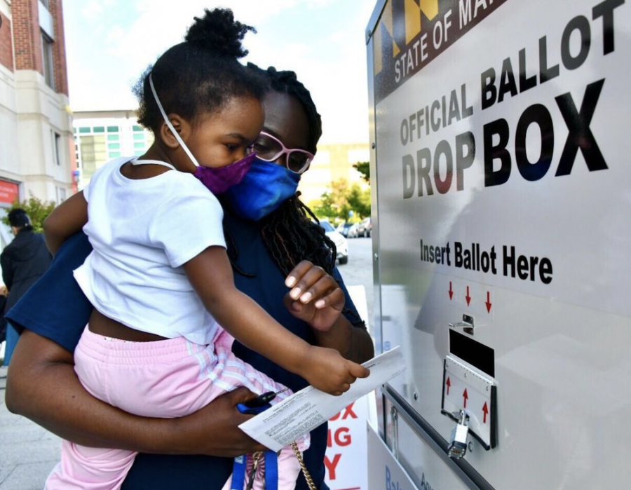 A voter drops in their ballot into the official ballot drop box. Many Americans used these ballot boxes located at polling stations to combat the long Election Day lines.