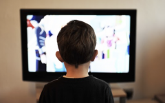 A young boy enjoys a DVD film. Before streaming services were created, many children used DVDS so they could watch their favorite films.