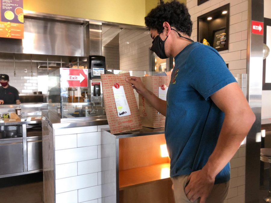A customer at Noodles & Company picks up their contactless order. Noodles & Company has been following COVID-19 restrictions closely and has made their online orders safer to obtain with contactless pickups and free food delivery through Nov. 15.