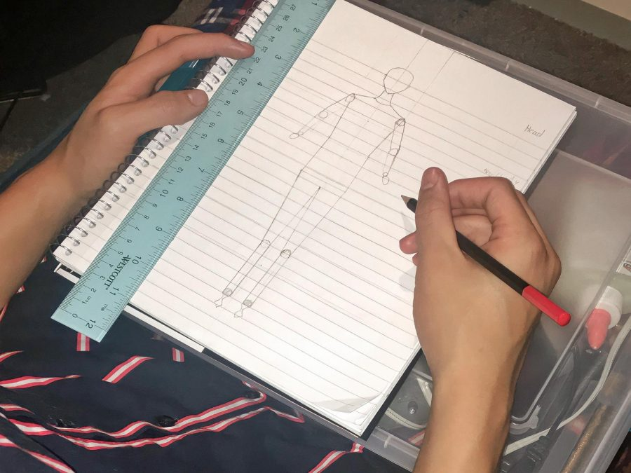 Junior Zachary Ramos sketches a croquis for Fashion Club. A croquis is a sketch that fashion designers draw to get an idea of what type of piece they want to create, something the club is working on as prep before designing.