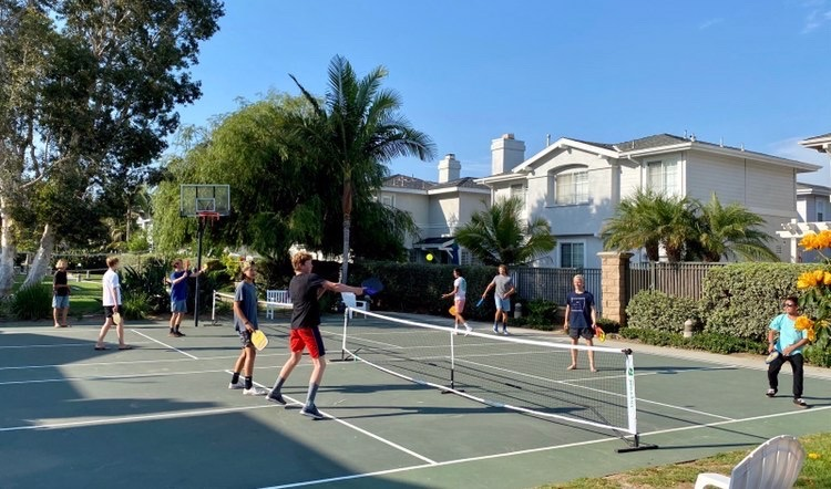 Wyatt and his friends are playing pickleball at a local court. He likes playing pickleball because everyone is pleasant to play with, and he often makes new friends.