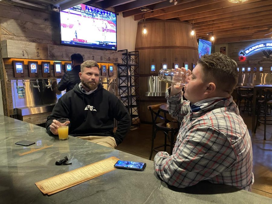 Two men are drinking in a local bar. Restaurants and other attractions have reopened, causing swarms of people to go back to their old normal.