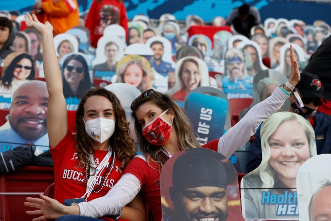 Two Tampa Bay Buccaneer fans with masks on are surrounded by cardboard cut-out fans in this year's Super Bowl. About 22,000 fans were allowed with regulations including masks on, spread-out seating, and temperature checks before entering the stadium.