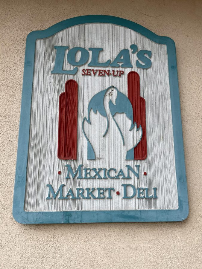 Lola's 7 Up Mexican Market and Deli sign is plastered to the side of the restaurant building. Lola's is a family-owned business that officially started selling their authentic Mexican food on March 17, 1986.