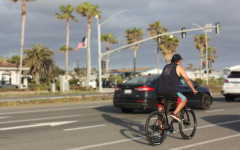 """A man stops at the light while cruising along the Carlsbad coast. Bicycling, as a whole, has seen a major increase in popularity that some call the """"bike boom""""."""