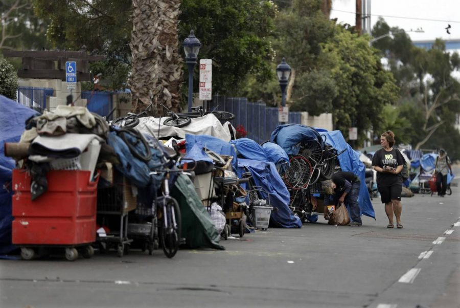 A homeless community sets up camp on the side of a busy San Diego road. Downtown areas are often overrun with full shopping carts and tents as many of these people have nowhere else to go.
