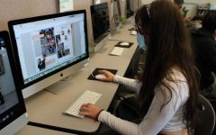 A Student works on composing a page of the Sage Creek yearbook while peers gather interviews and photos for the class around campus. In Publication Journalism, students work towards producing the end-of-the-year purchasable yearbook. They gather images and student quotes before composing every page with a theme in mind.