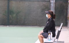 Coach Betsy Jordan watches over her players during their match against CCA. The girls tennis team expressed that Jordan is extremely supportive.