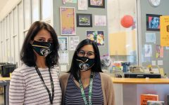 Shali (left) and DeLeon (right) pose in front of the librarians' desk. The two librarians have worked together previously at Aviara Elementary and Middle School, an experience which has strengthened their bond as counterparts and close friends.